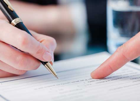 Un abogado especializado en derecho administrativo está escribiendo sobre un documento con información sobre materia administrativa.
