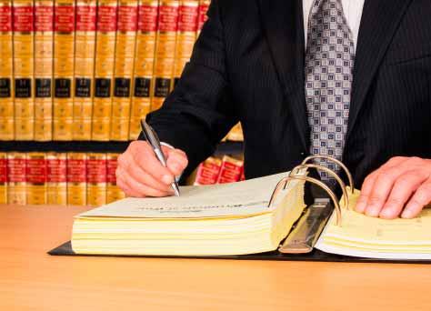 Un abogado civilista firmando unos documentos sobre derecho civil.