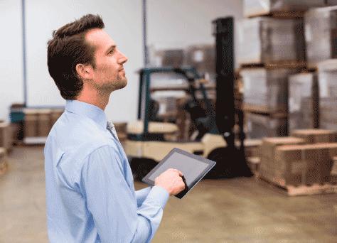 Una fábrica y una persona con una tablet con información en materia de derecho mercantil.