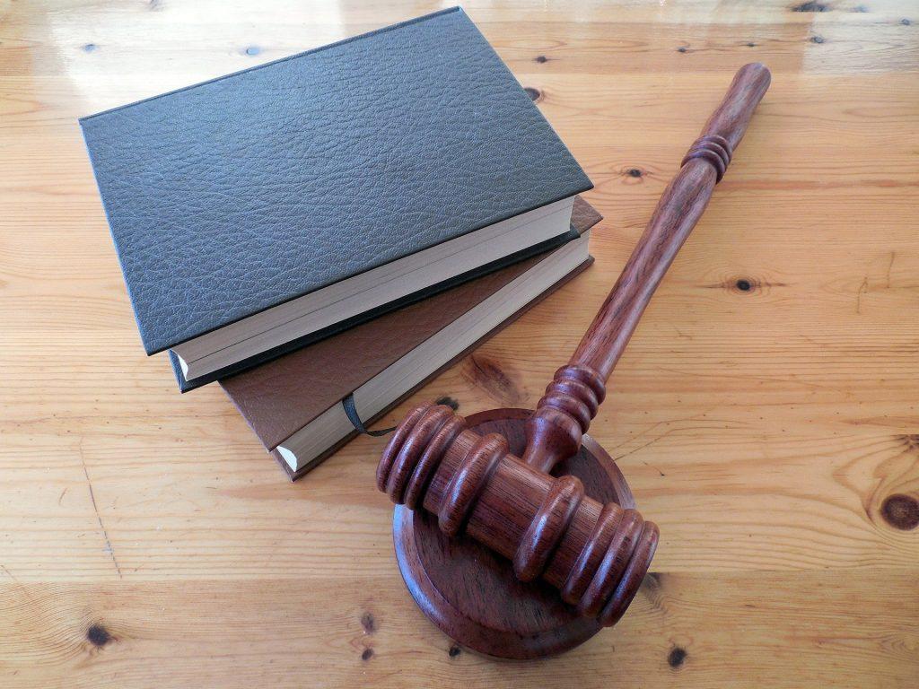Libros y un mazo en representación del derecho penal.