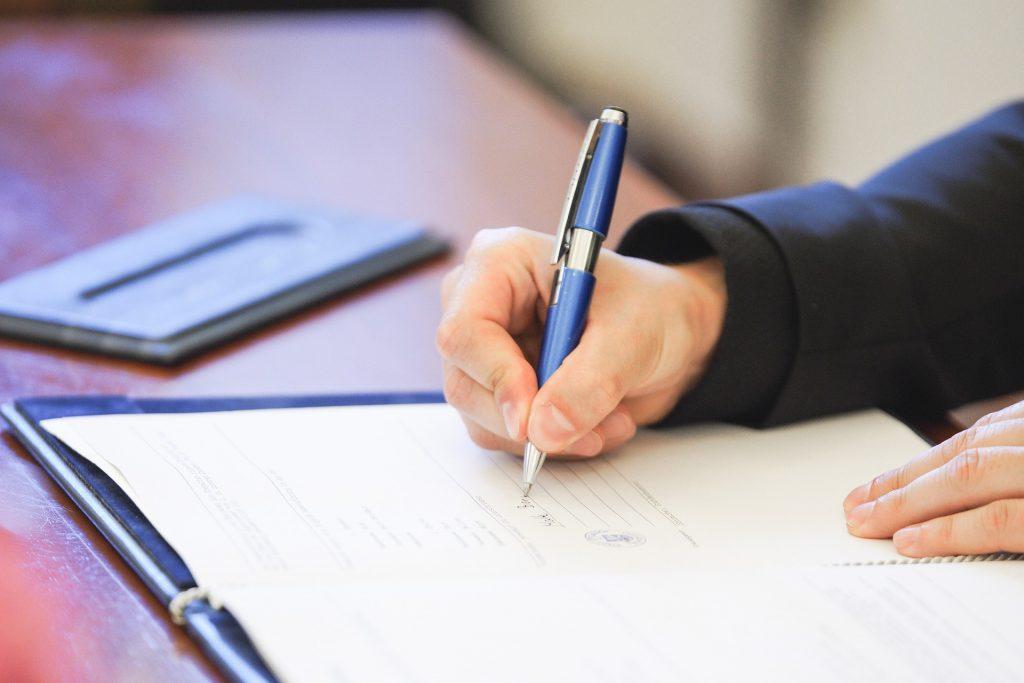 Un abogado laboralista en su despacho firmando unos documentos sobre asesoramiento laboral.