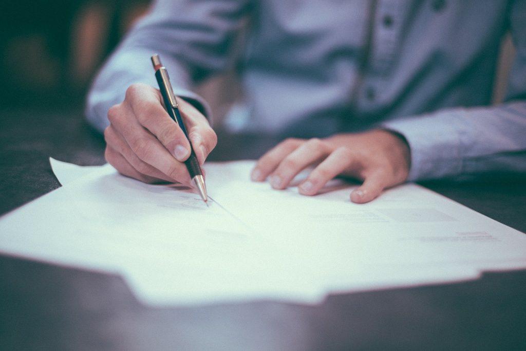 Un abogado especializado en derecho mercantil que está firmando unos documentos con información sobre asesoramiento en materia mercantil a empresas y emprendedores.